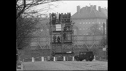 Menschen stehen auf einer Aussichtsplattform an der Bernauer Straße und schauen über die Mauer.
