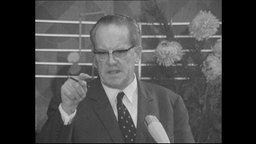 Der Politiker Herbert Wehner steht an einem Redepult und erhebt den Zeigefinger.