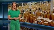 Panorama am 20.05.2021 mit Anja Reschke. Hinter der Moderatorin ist ein Bild einer Lagerhalle eines Online-Warenhauses eingeblendet. Unzählbar viele Pakete stehen in einer großen Halle.