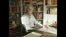 Ein älterer Mann sitzt in seinem Büro und spricht