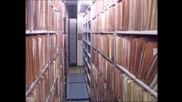 Ein Flur gesäumt mit Regalen und viel Archivmateriel