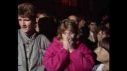 Eine Frau in pinker Jacke steht in einer Menschenmenge und hält sich die Hände vor ihr Gesicht (Artchivbild).