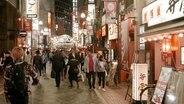 Eine Einkaufsstraße mit zahlreichen Leuchtreklamen in Tokio.