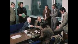 Männer sitzen und stehen um einen Tisch und beraten sich über Fahndungsfotos (Archivbild).