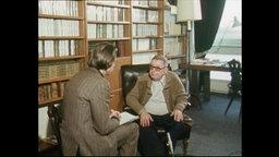Sartre und ein Reporter sitzen vor einem Bücherregal (Archivbild).