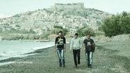 Drei Männer am laufen am Strand