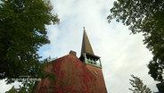 Ein Kirchturm vor bewölktem Himmel