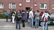Menschen stehen für eine Wohnungsbesichtigung Schlange