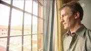 Ein Mann schaut durch ein vergittertes Fenster