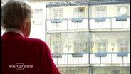 Eine Rentnerin steht an einem Fenster