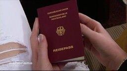Eine junge Frau hält ihren deutschen Reisepass in den Händen