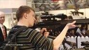 Ein junger Mann hält eine Waffe