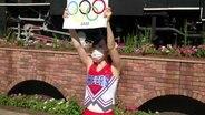Japanische Cheerleader halten Schilder mit dem olympischen Logo in die Luft.