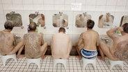 Unbekleidete, tätowierte Männer sitzen in einem öffentlichen Bad in Tokio vor Spiegeln.