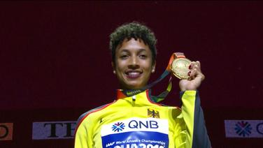 Eine Sportlerin zeigt ihre Medaille.