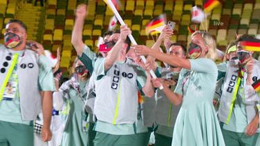 Beachvolleyballerin Laura Ludwig und Wasserspringer Patrick Hausding tragen die Deutsche Flagge.