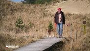 Ein Mann und sein Hund gehen am Strand von Amrum spazieren.