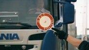 """Jemand hält eine Kelle mit der Aufschrift """"Halt Polizei"""" vor einen Lkw."""