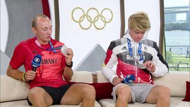 Jonathan Rommelmann und Jason Osborne betrachten ihre Silbermedaillen.