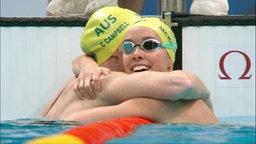 Zwei australische Schwimmerinnen umarmen sich.