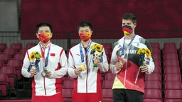 Die drei Medaillengewinner stehen zusammen auf dem Siegertreppchen.