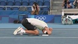Der Tennisspieler Alexander Zverev kauert in Freudenpose auf dem Tennisplatz