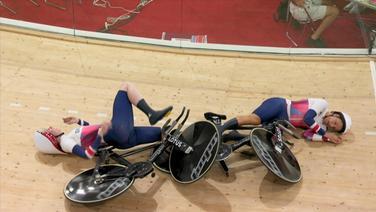 Zwei Radsportlerinnen liegen nach einem Sturz auf dem Boden.