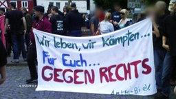 """Banner mit der Aufschrift """"Wir leben, wir kämpfen für Euch gegen Rechts"""""""