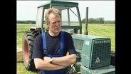 Ein Bauer steht vor einem Traktor