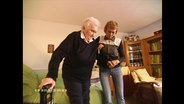 Eine Pflegekraft stützt eine Seniorin