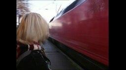 Eine Frau auf dem Bahnsteig