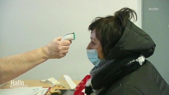 Temperatur bei einer Frau wird gemessen.
