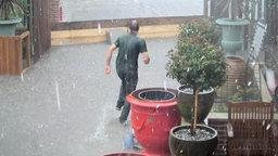 Ein Mann läuft bei Regen durch Hochwasser