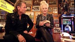 Peter Maffay sitzt bei Inas Nacht mit Ina Müller auf einem Tisch.