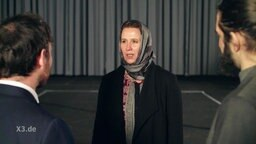 Frau mit Kopftuch steht vor zwei weiteren Personen.