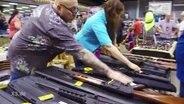 Zwei Menschen fassen Waffen an