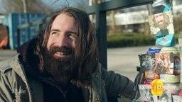 Ein Obdachloser Mann vor einem Turm von Dosen.