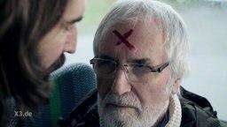 Auf dem Kopf eines älteren Mannes steht ein X in Rot geschrieben.