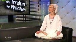 Foodbloggerin und Diät-Beraterin Kirstin Warnke sitzt in einem weißen Gewand mit Turban auf einer schwarzen Couch.