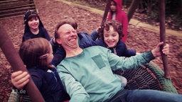 Dennis Kaupp auf einer Schaukel mit Kindern