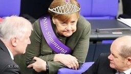 Angela Merkel mit Diadem und Schärpe.