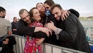 Alina Stiegler wird von Rasmussen und seiner Band umarmt