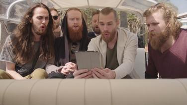 Der dänische Sänger Rasmussen (Zweiter von Links in der vorderen Reihe), sitzt mit seiner Band im Tuktuk und singt.