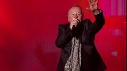 Jim Kerr von den Simple Minds singt auf der Bühne.