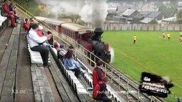 Eine Dampflock fährt direkt am Spielfeldrand eines Fußballplatzes