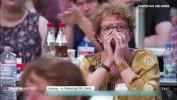 Ein Parteimitglied der Linken hält sich vor Entsetzen die Hände vors Gesicht