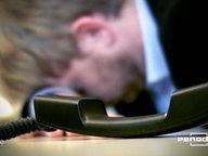 Eine Person schlägt mit der Stirn auf einem Schreibtisch auf. Daneben ein Telefonhöhrer.