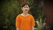 Kleiner Junge mit aufgeklebten Bart in der Rolle als Erdogan.