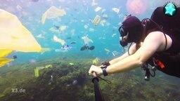 Ein Taucher filmt die Unterwasserwelt: Zu sehen sind viele Plastikteile und Tüten.