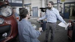 Ein Chef in einer KFZ-Werkstatt meckert seine angestellten Mechaniker an.